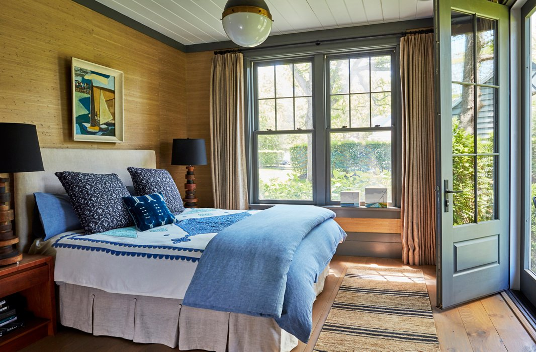 A painting from a flea market in Saint-Tropez crowns a linen-upholstered bed. Soft gray trim frames the seagrass-covered walls, while mismatched bedding in shades of indigo reflects the hues of Wooley Pond.