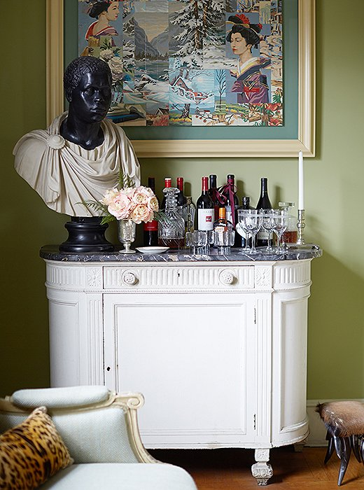 A perfectly Sheila vignette: A framed piece of outsider art hangs above a classical bust on the bar.