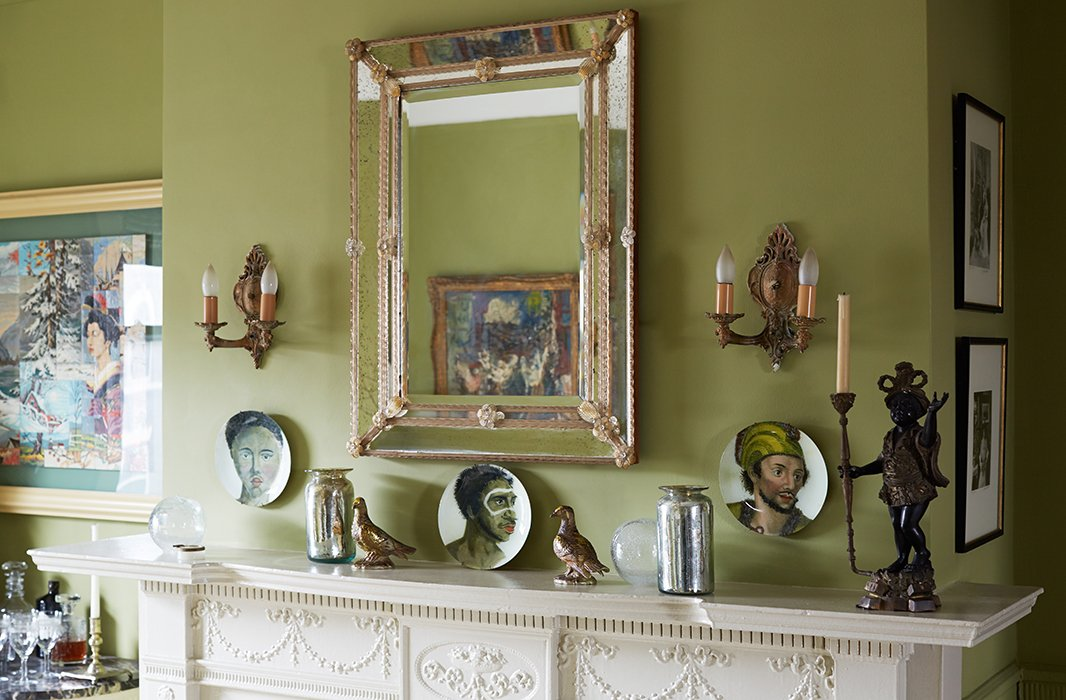 Sheila's collection of Venetian glass includes this mirror, accompanied by a series of John Derian plates. Another dining room wall features a set of Hermès plates.