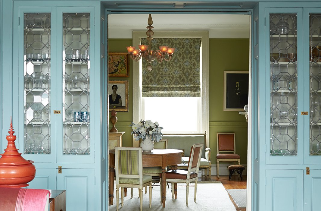 An apple-green dining room plays nicely with adjacent blue-painted cabinets in the Harlem home of designer Sheila Bridges. Photo by Manuel Rodriguez.