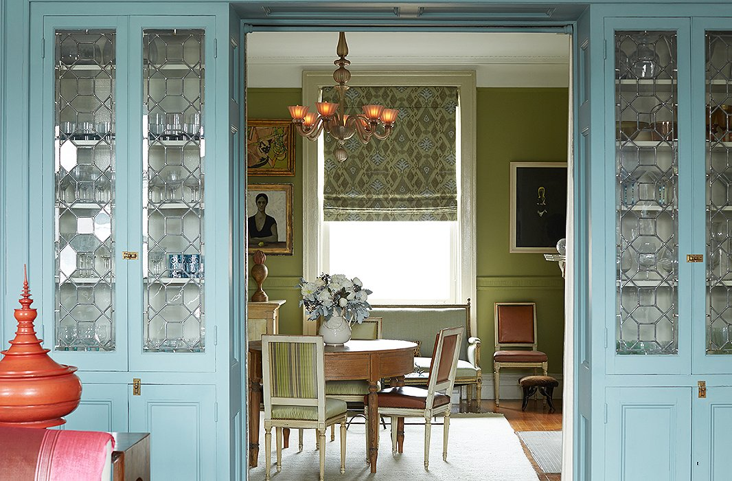 "Blue-painted cabinets, which house glassware Sheila inherited from her parents and grandparents, divide the living room from the dining room. Sheila calls the dining room's color a ""Granny Smith apple green."" Find similar dining chairs here."