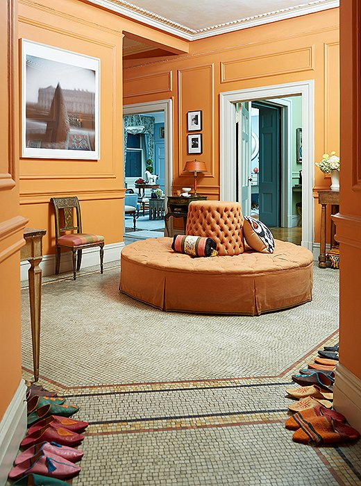 To mirror the orange tiles, Sheila placed an orange borne in the center of her entryway. In the foreground sit the Moroccan slippers that everyone wears inside.