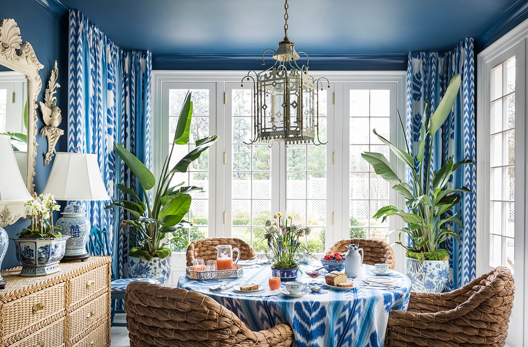 Woven water-hyacinth chairs of Danielle's own design give the breakfast room a gardenlike atmosphere, enhanced by the peacock-blue walls and potted banana plants.