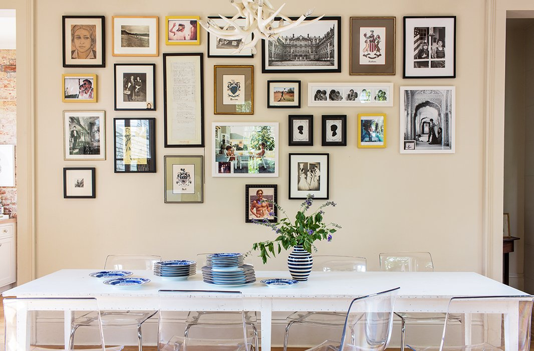The gallery wall gets a modern update thanks to the alignment of works at the top of the arrangement. Photo by Nicole LaMotte.