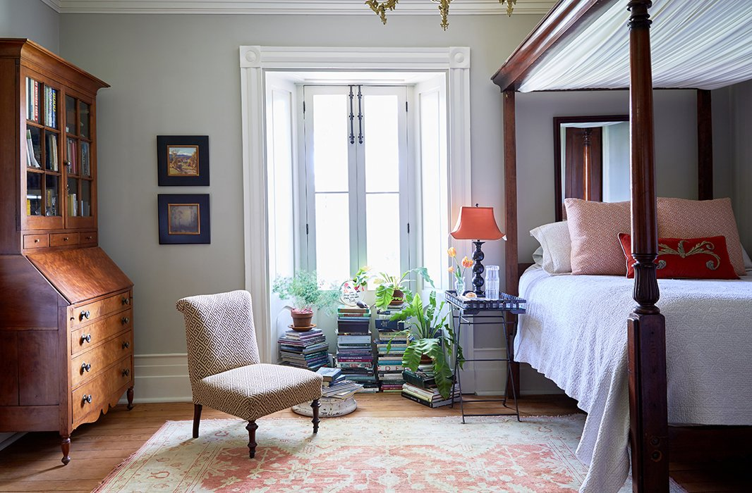 In the corner of the master bedroom, a secretary desk lends a sense of symmetry opposite the refurbished canopy bed.