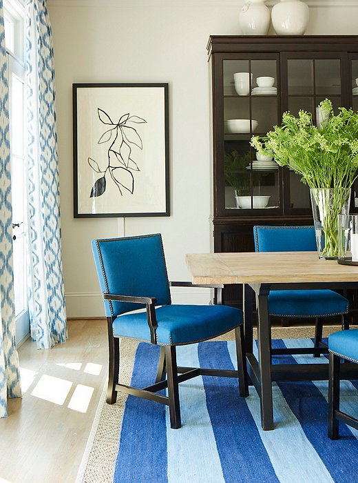 Touches of black add depth to a blue-and-white dining room, featuring pieces by Mark D. Sikes for Henredon.