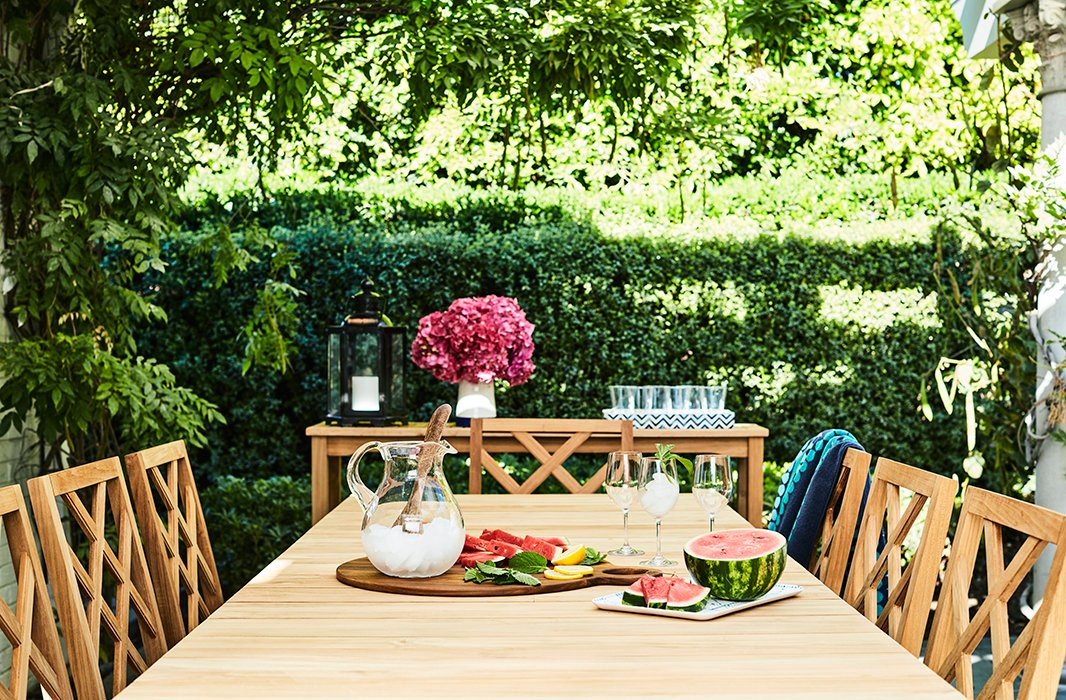 Beneath a pergola designed by Kaling's father, Avu, sits another table surrounded by chairs backed with an updated chippendale motif. A console anchors the far end, serving as a bar or buffet alfresco.