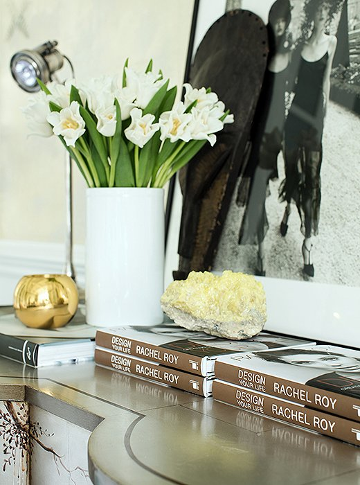 """A fashionable vignette atop the chest includes agold matchstriker by AERIN, a print purchased at a Vogue auction, and araw yellow crystal that """"promotes balance,"""" Rachel says."""