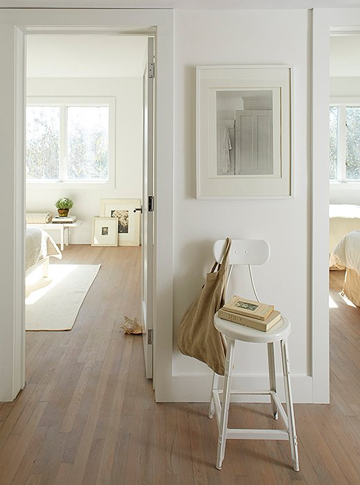 "A steel stool sits beneath a still life matted and framed in two tones of white. Foley had the floors refinished to feel ""modern and warm."""