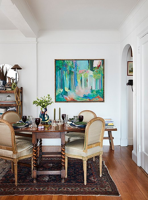 "A drop-leaf table with spindle legs is centered on top of a vintage rug. Secondhand French chairs upholstered in tattered silk were the perfect size for the small space. ""Our home is a mix of styles,"" says Matt, ""and it's materialized in a very organic way—everything works, but nothing was planned."""