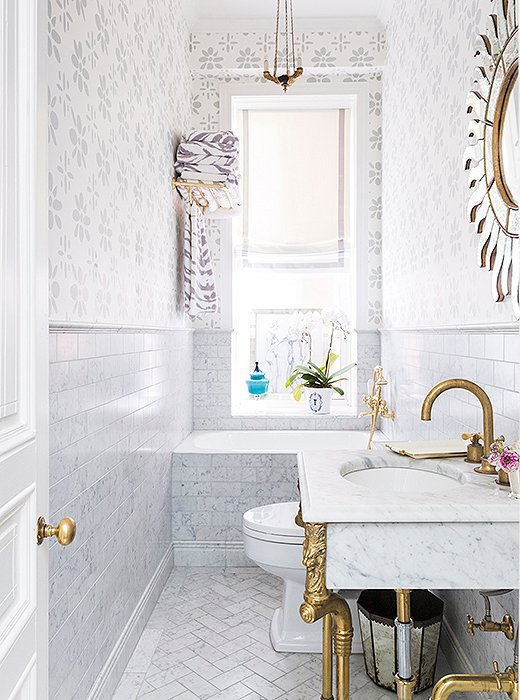 Designer CeCe Barfield livened up this petite bath with wallpaper custom-colored to match the tones of the marble tile. The resulting monochromatic look helps the space feel more expansive. Photo by Lesley Unruh.
