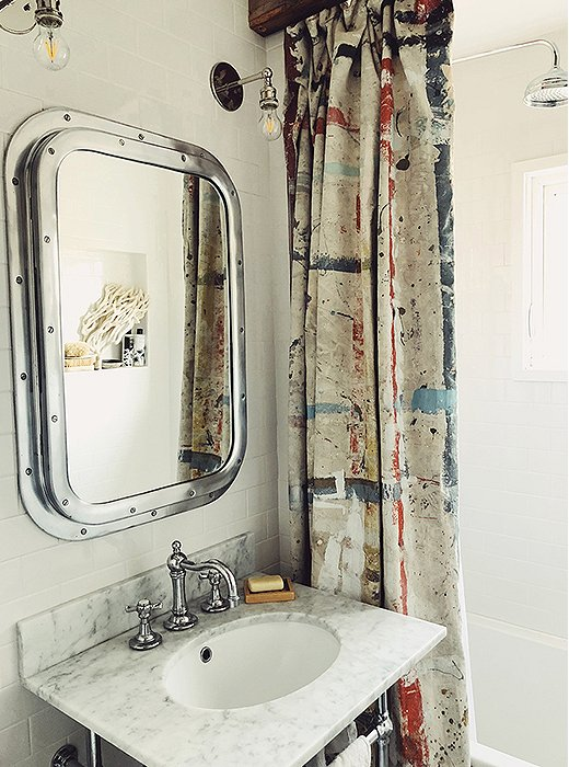 A riveted chrome mirror lends nautical charm to the bathroom, accented with found coral and an artfully paint-splattered shower curtain. White subway tiles keep the look bright and fresh.