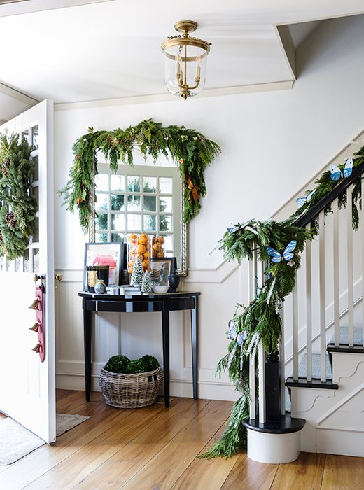 In the foyer, a traditional evergreen garland goes whimsical with a mix of fresh foliage and woodland-inspired trimmings.