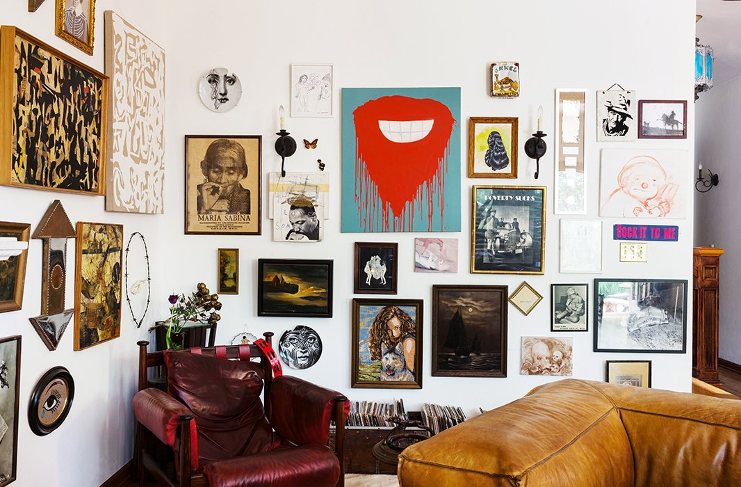 A medley of wall plates, sconces, paintings, prints, and drawings makes for a wonderfully eclectic gallery wall.  Photo byNicole LaMotte.