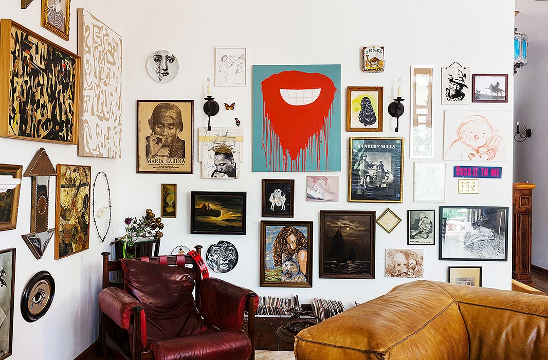 A medley of wall plates, sconces, paintings, prints, and drawings makes for a wonderfully eclectic gallery wall.  Photo by Nicole LaMotte.