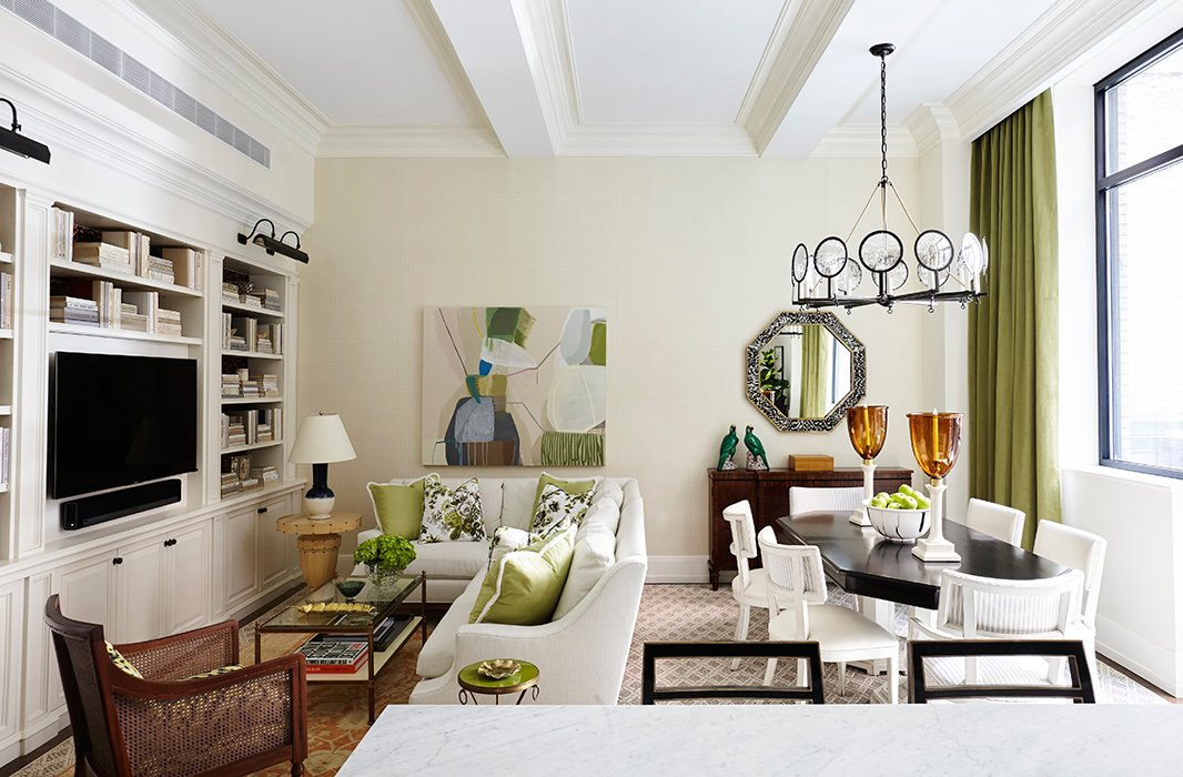 Georgie and Jen freshened the living room walls with a coat of Benjamin Moore's Acadia White. A scaled-down sectional separates the living and dining areas, while accents of green help unify the open-plan space.