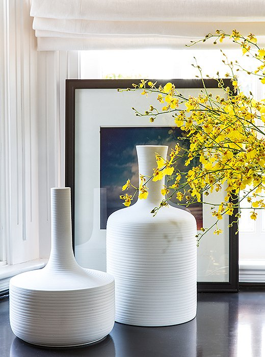 Don't limit beautiful objects to the rest of the house—putting eye-catching pieces, like these glowing white vases, in the office helps make it a place you actually want to spend time in.