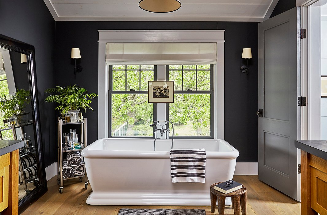 Deep-charcoal walls and crisp white trim add drama to the master bath. A pen-and-ink drawing from an antiques store in Milwaukee creates a focal point above the luxurious tub.