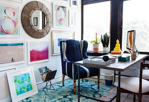 A minimalist desk is a quiet complement to a vivacious wingback chair and a lively gallery wall. Photo by Nicole LaMotte.