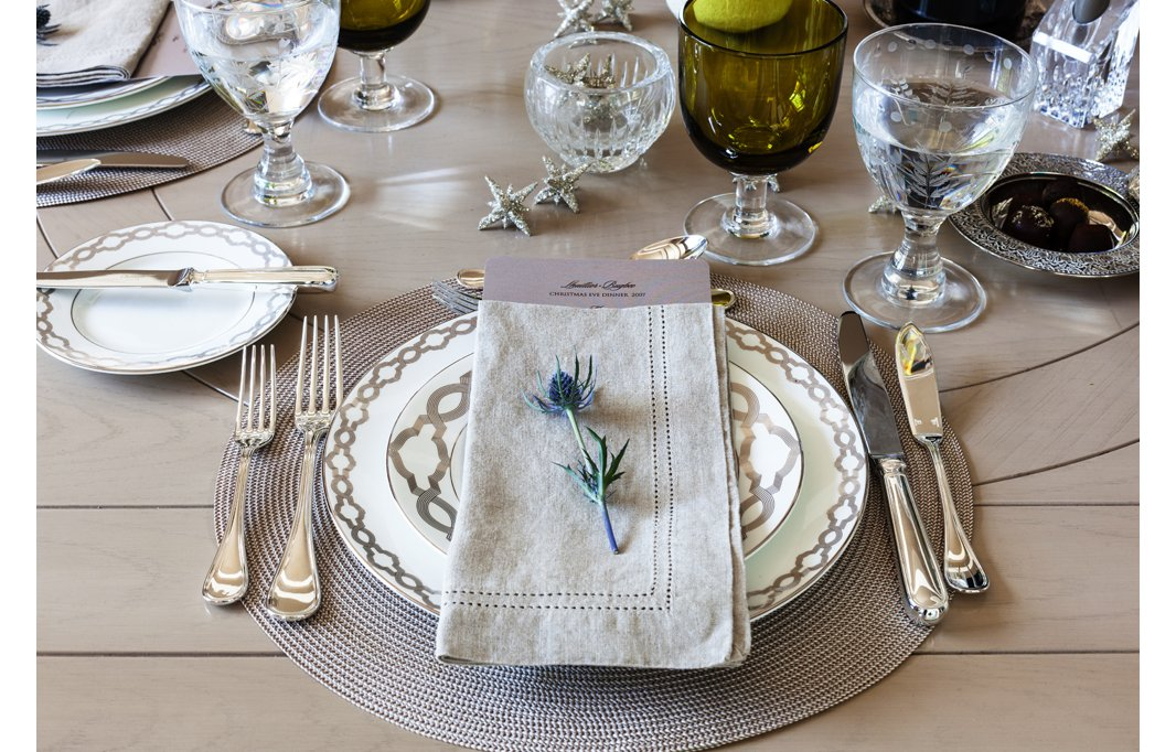 Set a luxurious scene with silvery designs and etched glassware. A few colorful touches—such as a fresh flower and hunter-green drinkware—keep it interesting.