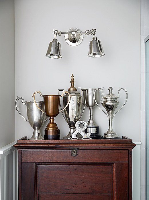 "A grouping of trophies—and, okay, a busted $4 coffeepot—makes for an unexpected vignette, especially in a powder room. ""I just put them together,"" says Barbara, who tried using actual family trophies (her daughter is a world-class swimmer) before determining that they didn't look right. ""These are more like loving cups,"" she says."