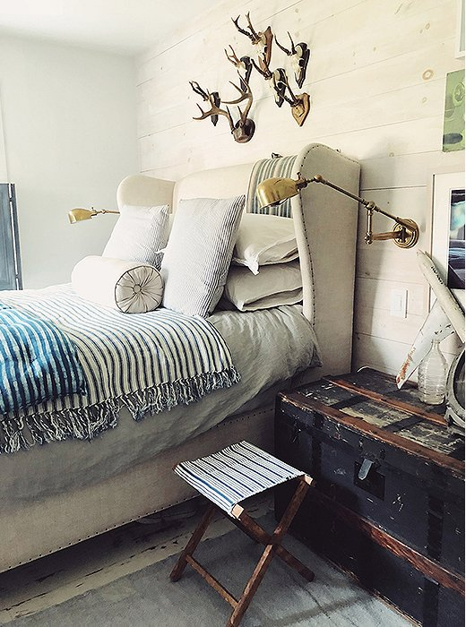 "The bedroom is awash in airy neutrals, with hints of coastal blue and green. The layered bedding—including two lightweight blankets in indigo stripes—feels inviting and relaxed. ""In Tulum, I discovered I loved blue and indigo, and I keep a lot of textiles thrown around,"" says Dean."