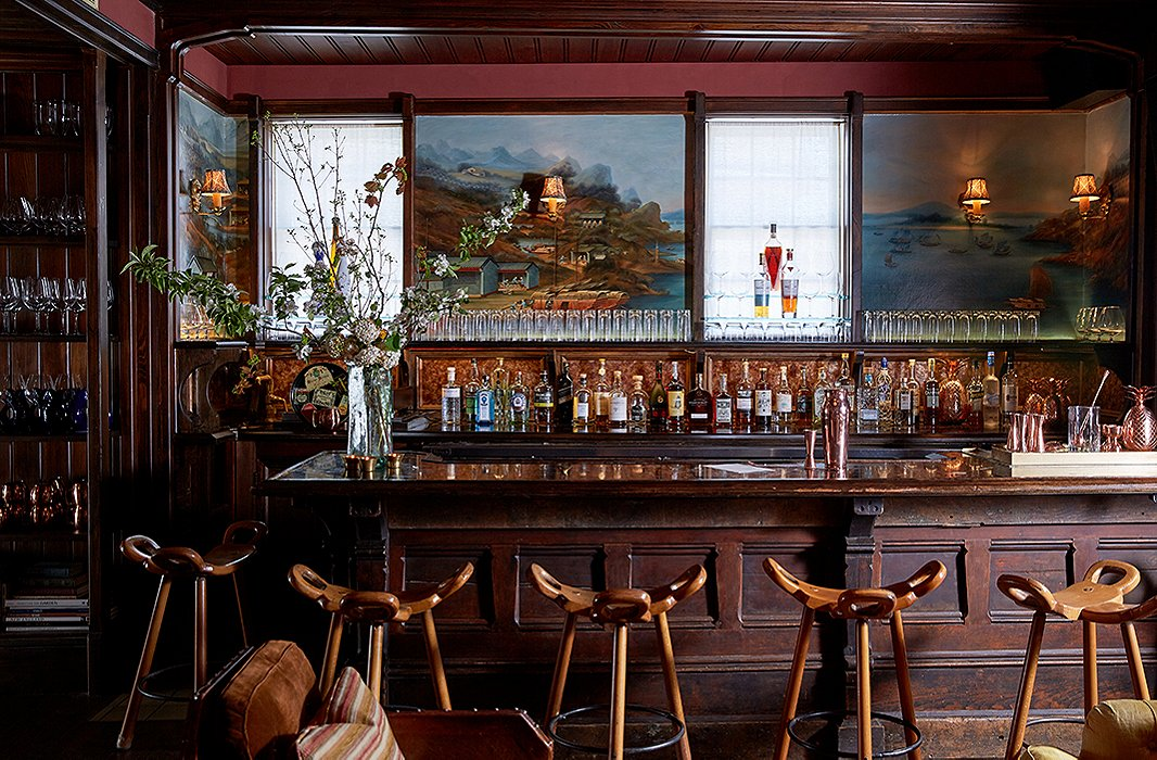 The paneled bar was sourced from the Midwest and topped with a wood-trimmed honed-marble slab. The scenic panels behind the bar, by New York decorative painter Dean Barger, take inspiration from a painting in the Peabody Essex Museum and depict historic Chinese merchant ports.