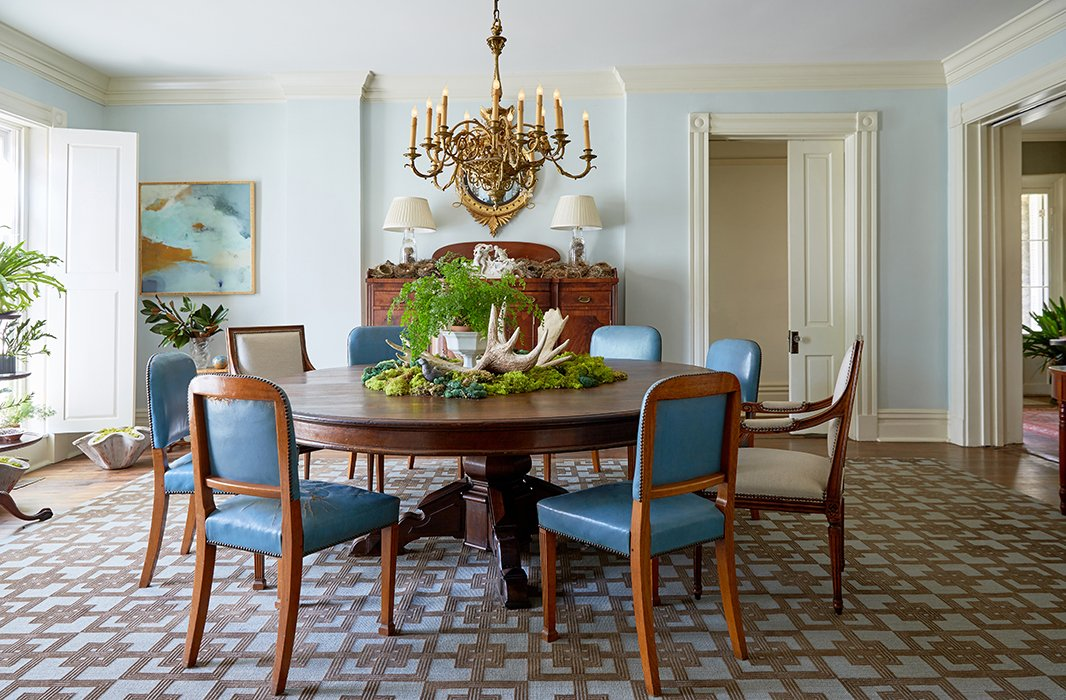 "A pedestal table for 12 surrounded by mismatched chairs is centered under a brass chandelier. The centerpiece is changed out seasonally but remains consistently green in warmer months. ""Moss, ferns, whatever's available I tend to use,"" Jon says. Behind, a sideboard covered in birds' nests collected from transplanted trees minimizes any sense of formality."