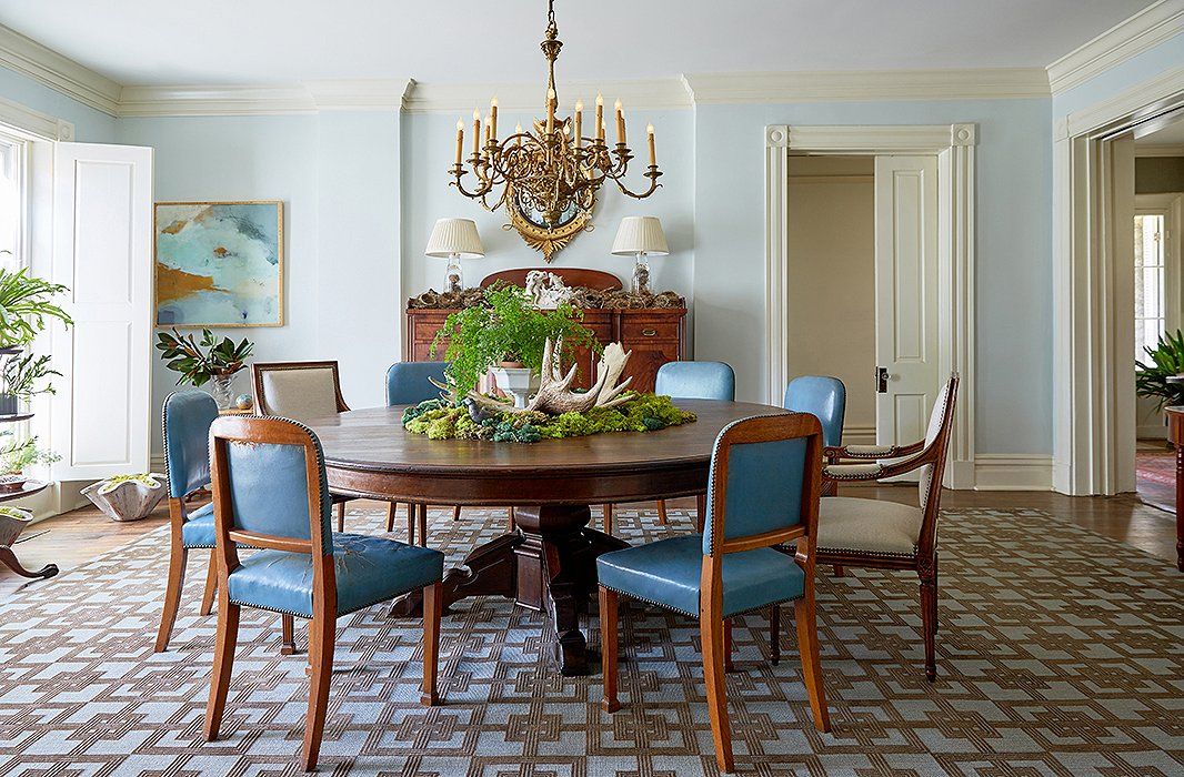 """A pedestal table for 12 surrounded by mismatched chairs is centered under a brass chandelier. The centerpiece is changed out seasonally but remains consistently green in warmer months. """"Moss, ferns, whatever's available I tend to use,"""" Jon says. Behind, a sideboard covered in birds' nests collected from transplanted trees minimizes any sense of formality."""