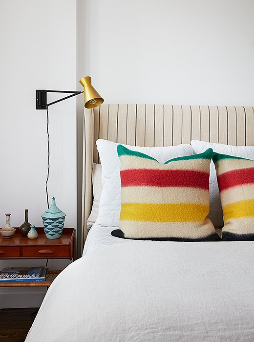 "A guest-room bed serves as an experiment in scale. The bold primary stripes of the pillows work with the headboard's fine lines to create maximum visual interest. ""It's a poppy room,"" notes Sally, ""and I think it represents the side of her that's more laid-back. Everything here was about comfort, color, and texture."""
