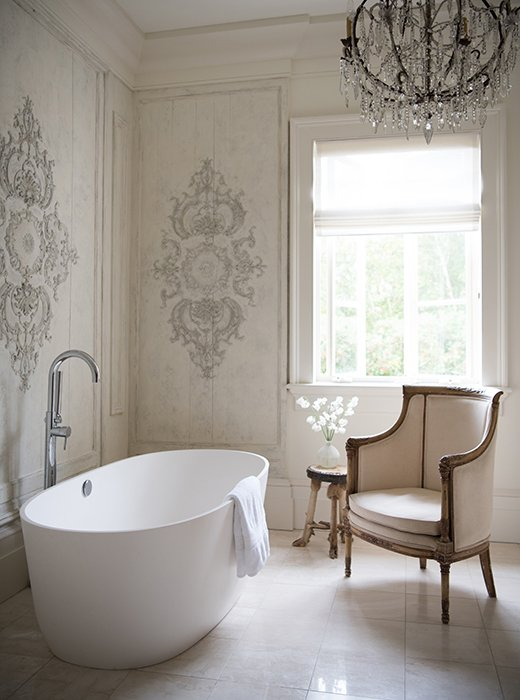 Timeless French Decorating Ideas {Tara Shaw}. Tara describes herself as a tub girl - she takes a bath nightly with Epsom salts and lots of potions and notions.The furnishings of this little retreat distill her grand but accessible style: a contemporary tub, a chandelier, and a bergere (from her own line). For the walls, she installed three pieces of paneling she'd found in the South of France. There wasn't quite enough of it, so we built it out with pine and did a finish on top, so you can't tell the old from the new.