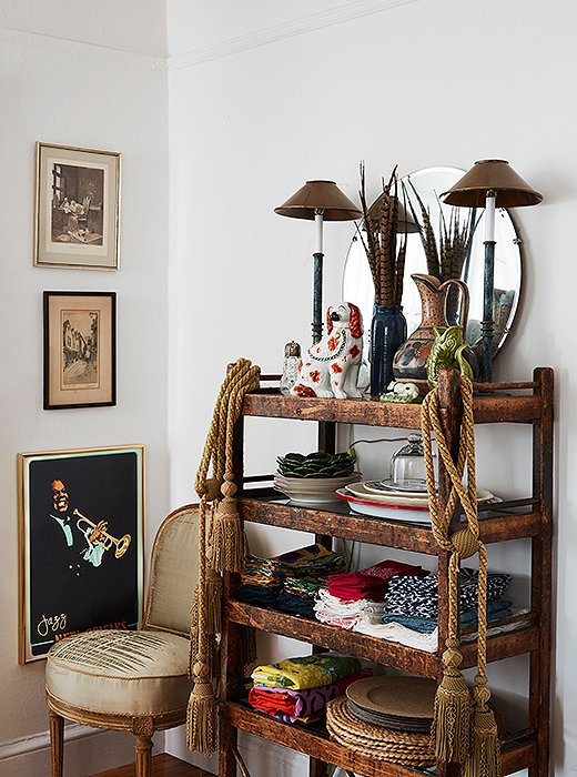 A cart drapedwith tassels hosts napkins, not liquor. On top, a Staffordshire dog holds court between two buffet lamps in front of pheasantplumes and a vintage mirror.