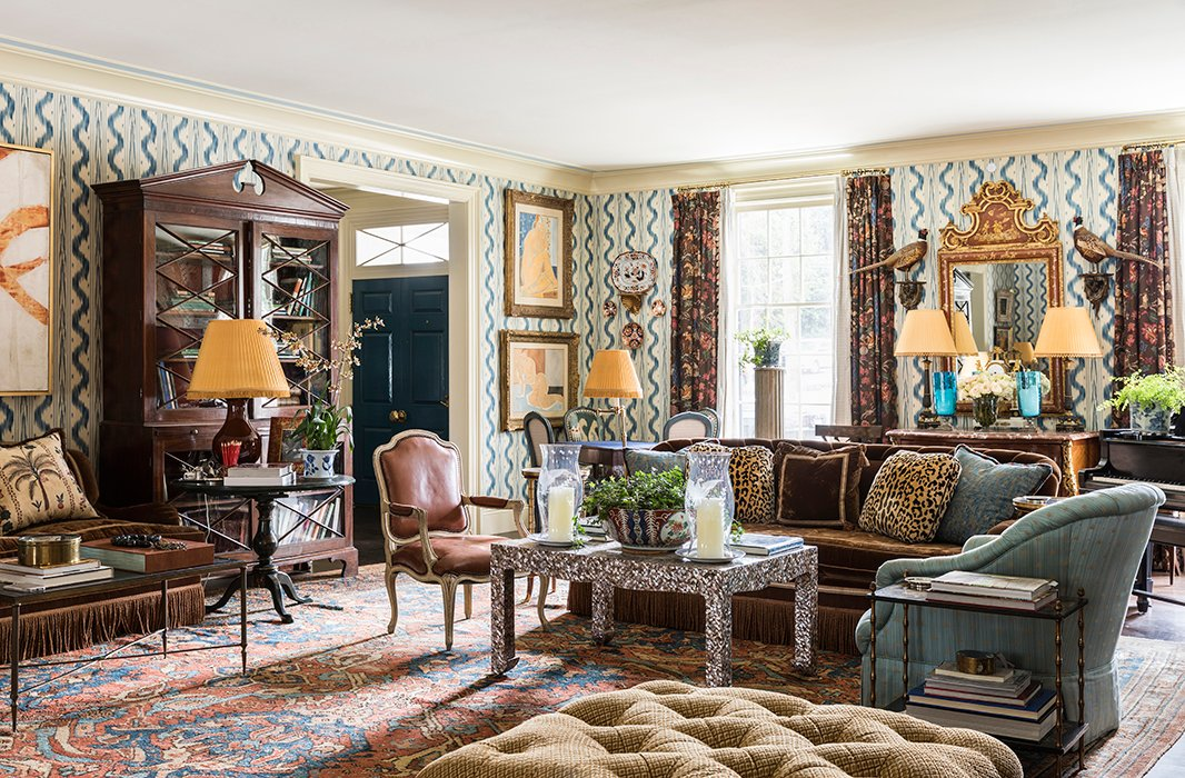 In the salon-style living room, sofas in Prelle silk velvet define the main seating areas. Patterns varying in scale but similar in tone (see the ivory-and-blue Pierre Frey wall covering, leopard-print pillows, and perfectly worn antique rug) were carefully chosen to complement, not clash.