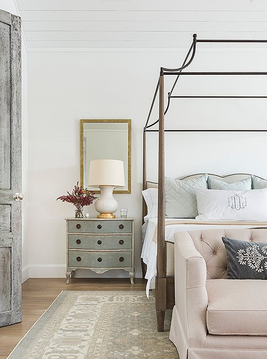 A beautifully distressed door leads to the master bedroom, where a graceful canopy bed makes the most of the soaring ceiling. Photo by Julie Soefer.