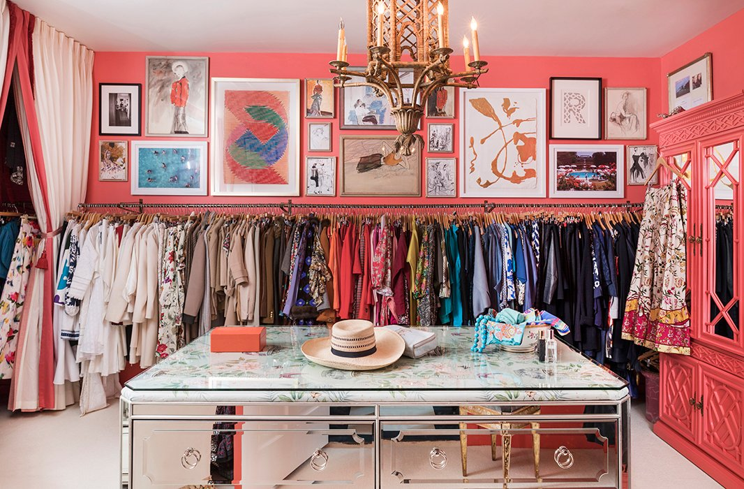 The closet features a mirrored island with an upholstered top under glass. The walls glow in a coral hue similar to that of Danielle's favorite lipstick, Grace by NARS.