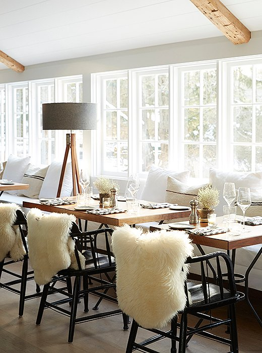 Sheepskins add softness to the glossy dining chairs, paintedto achieve a lacquerlike effect.
