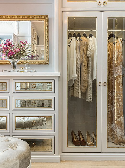 A mix of clear glass and antiqued mirror gives the master closet a glamorous feel (while keeping clutter hidden away). Photo by Julie Soefer.