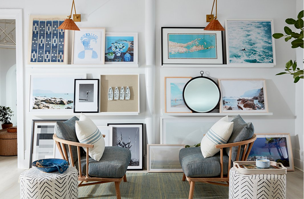 A mix of artwork casually leaned on floating ledges (and on the floor below) gives this space a relaxed yet polished feel.