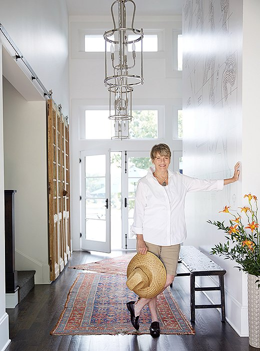 "Barbara didn't feel that the house's layout lent itself to an overly formal entryway, but she created a nice welcoming moment here, pairing several of her own tiered pendant fixtures with natural woods and casually overlapping carpets. ""Those are my husband's family's rugs. They're pretty thin and pretty worn, and I love them that way,"" she says."