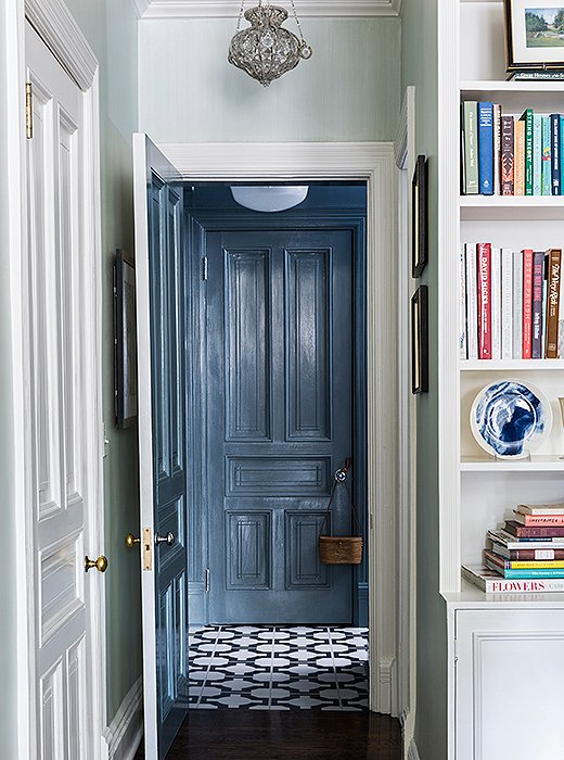 A palette of calming blues runs throughout the apartment, from the living room's pale sky walls to the patterned tiles and slate-tone woodwork off the kitchen.