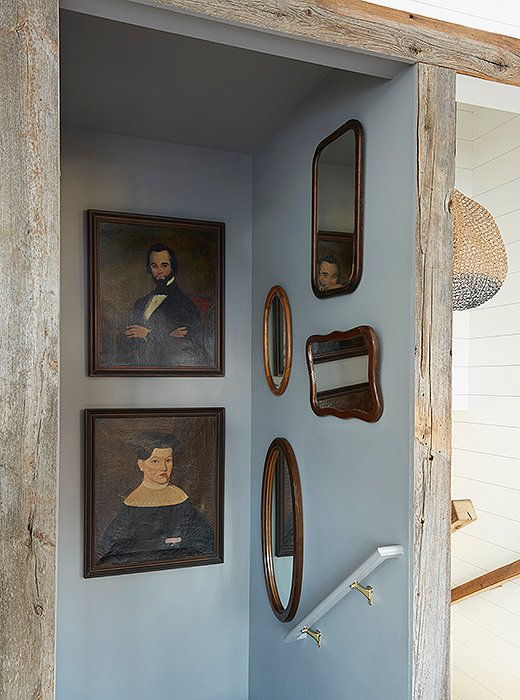 A stairway leading to the kitchen is accented with vintage artwork and mirrors. The portrait at bottom left was repaired with a Band-Aid—a cheeky solve that turns a traditional touch into a contemporary showstopper.