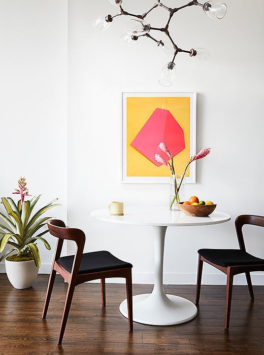 A colorful print (Monolith I by David Grey) adds a splash of Palm Springs glam to an iconic Tulip-style table in white (find a similar one here) and dark midcentury-style chairs. Design by One Kings Lane Interior Design. Photo by David A. Land.