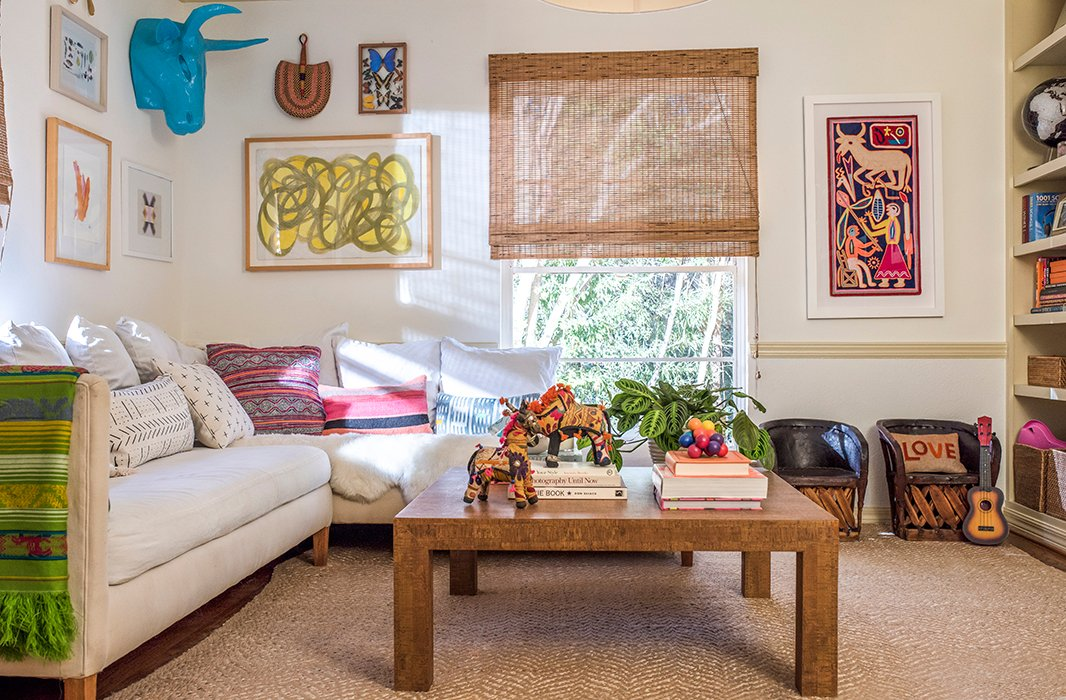 Colorful art and a layer of patterned pillows brighten up the playroom's neutral foundation.