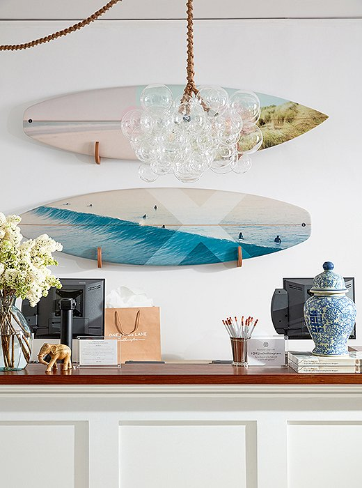 A pair of surfboards featuring artwork by Christine Flynn makes for unexpected wall decor. A chandelier by The Light Factory evokes the bubbling surf.