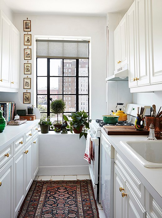 Simple, clean, and to the point, the apartment's galley kitchen was personalized with brass knobs, artwork, and a Persian runner.