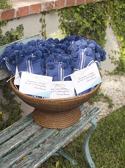 "Susan filled a basket with bundled-up light blankets, both in case guests became chilly as the night carried on and as a parting gift for them to bring home. Attached with a quote from author Charles Bowden—""Summertime is always the best of what might be""—each was a charming ode to the season."
