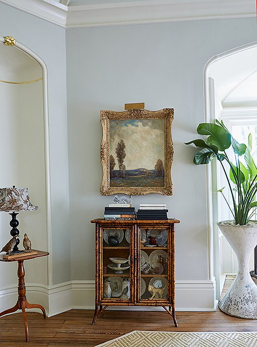"A Brighton-style bamboo cabinet sits beneath an English oil painting. ""The art helped inform the room's wall color,"" says Jon, but it was Dale who chose all the swatches. In this case, Sherwin Williams's Aloof Gray provides a cool contrast to the space's brassier hues."