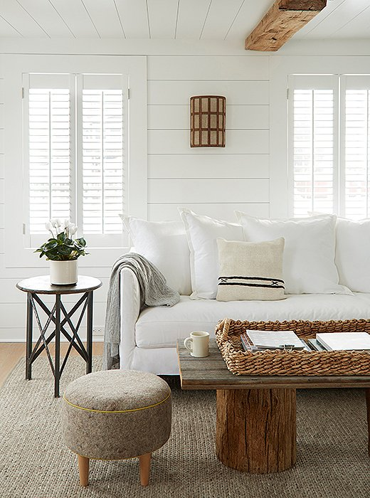 In the Webster room, a sofa slipcovered in white canvas rests on a braided wool rug. A custom coffee table anchors the cozy lounge spot.