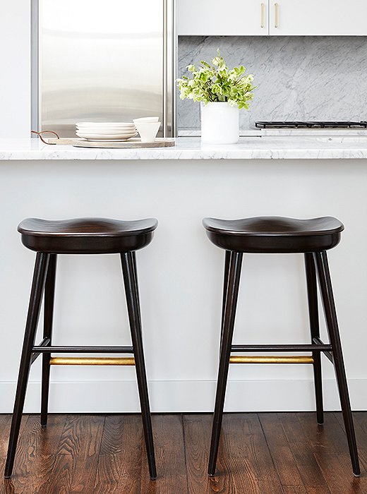 "Brass details on two barstools by Brownstone provide a pleasant contrast to the kitchen's stainless-steel finishes. ""Even without a back, they're probably the most comfortable I've ever sat in,"" Sally says."