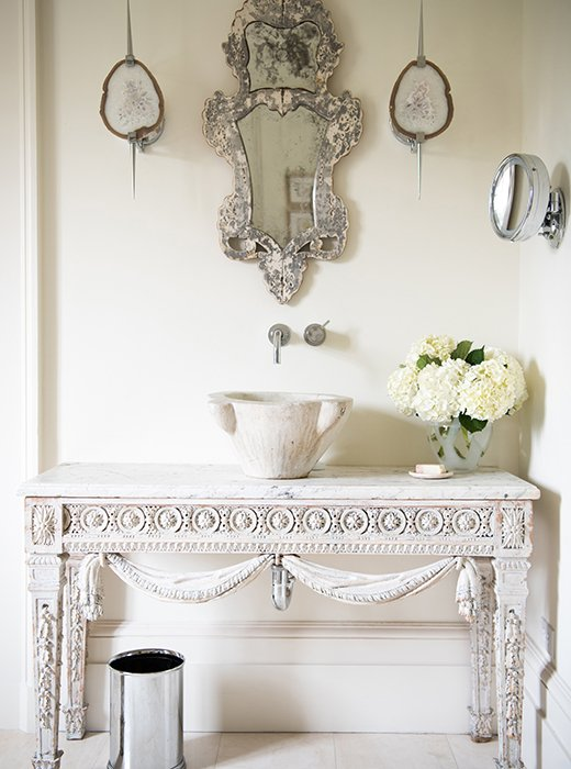 Timeless French Decorating Ideas {Tara Shaw}. Tara created a bathroom sink to her taste by converting an Italian mortar to a sink and installing it in a white vanity table. AVenetian mirror hangs above it.